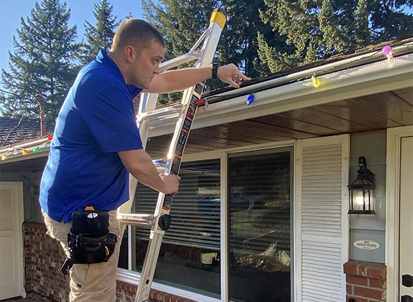 Lee Doran, from Doran Home Inspections, on a ladder inspecting a roof